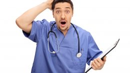 Surprised young doctor in blue uniform